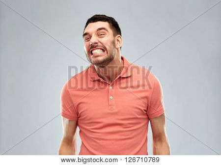 emotion, cruelty, anger and people concept - angry man over gray background
