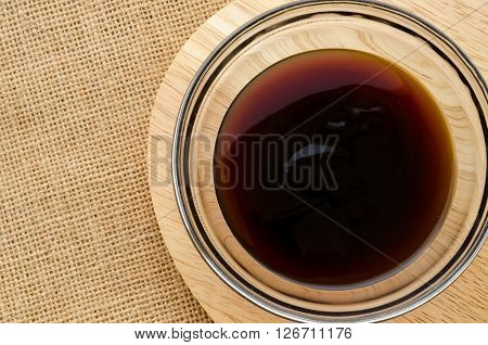 Oyster sauce in glass bowl on sack background.