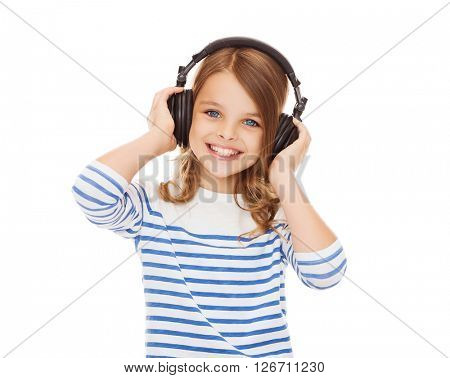 people, children and technology concept - smiling girl with headphones listening to music