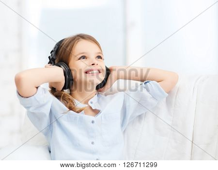 people, children and technology concept - smiling girl with headphones listening to music at home