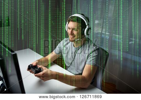 technology, gaming, entertainment, let's play and people concept - happy young man in headset with controller gamepad playing computer game at home and streaming playthrough or walkthrough video
