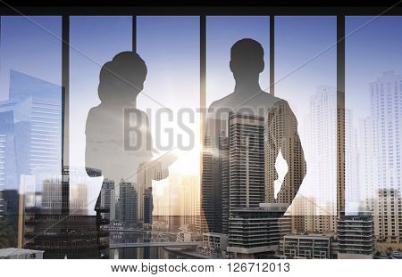 business, partnership, teamwork and people concept - silhouettes of partners over double exposure office and city background
