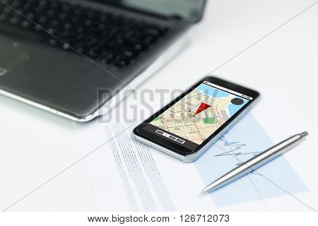 business, technology, navigation and location concept - close up of smartphone with gps navigator map on screen, laptop computer and pen on office table