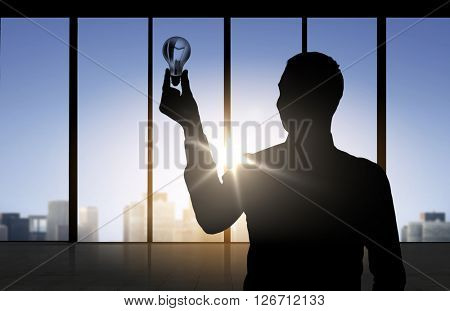 business, inspiration, idea and people concept - silhouette of businessman holding light bulb over office window background