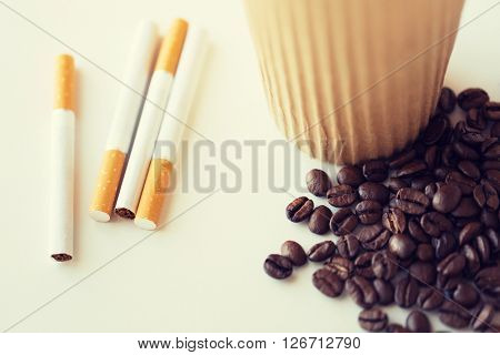 bad habits, addiction and unhealthy lifestyle concept - close up of cigarettes, coffee cup and beans on table