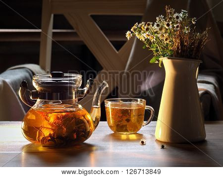 Green tea is brewed in a transparent teapot. Tea leaves in the form of a flower. On the table with a cup of tea and a bouquet of flowers in a jug. Still life. Chamomile flowers and spikes. Evening, evening light