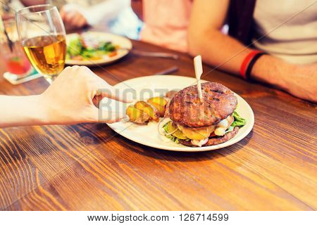 people, leisure, friendship, eating and food concept - close up of friends hands with burger at bar or pub