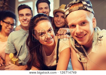people, leisure, friendship, technology and party concept - group of happy smiling friends with smartphone and drinks taking selfie at bar or pub