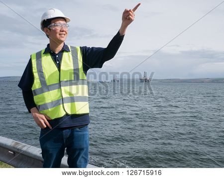 An asian engineer pointing and smiling and standing in front of semi submersible oil rig