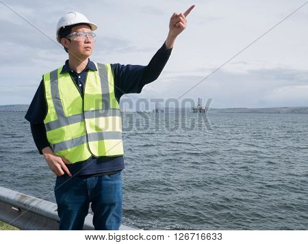 An asian engineer pointing and standing in front of semi submersible oil rig