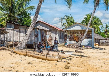 Ambatozavavy Nosy Be Madagascar - December 19 2015: Locals relax in the shade near traditional wood pirogue with outrigger in the village of Ambatozavavy on the island of Nosy Be Madagascar. Traditional fishing village on Nosy Be island with wooden dugout