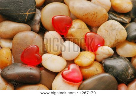 Pebbles At The Background And Red Heart Shapes