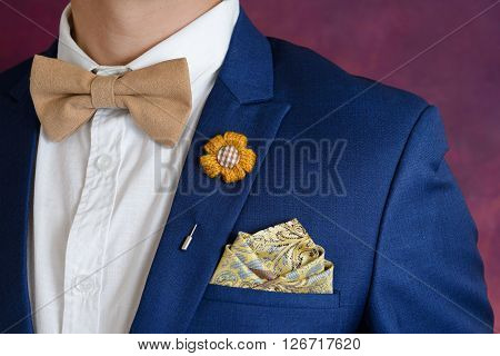 Man in blue suit with brown bow tie flower brooch and classic texture pocket square close up