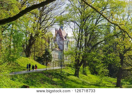 Chynadiyovo, Zakarpattia Oblast, Ukraine - April 16, 2016: Several tourists in the park on the road to the former Carpathian residence and house hunting Count Schönborn of the 19th century in spring day.