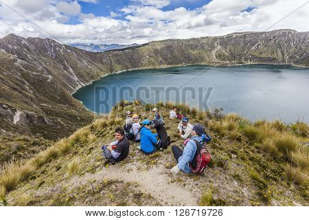 ZUMBAHUA ECUADOR - APRIL 15: Group of hikers walking around the crater of Quilotoa lake taking a break on april 12 2014 Zumbahua Ecuador