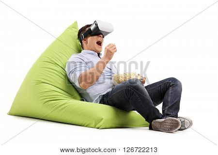 Young man eating popcorn and watching something on a VR goggles seated on a beanbag isolated on white background