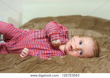 Baby boy lying on belly. Cute year-old kid with interest looks and smile, boy lying on bed in the bedroom with white linens. Home interior in the background.