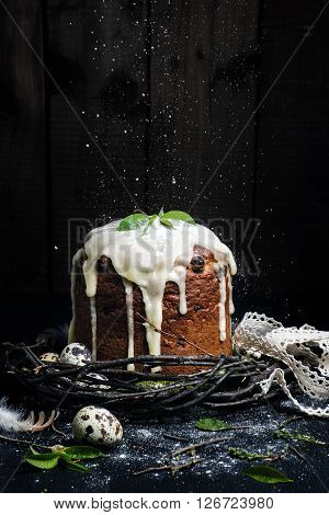 Easter cake on dark background with quail eggs in wreath of twigs with leaves. Powdered sugar on top fray as snow