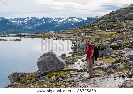 man walking on a mountain trail in Norway. Path to Trolltunga or Troll tongue
