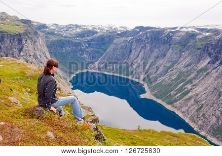 woman looking at the lake in the mountains Norway. Path to Trolltunga or Troll tongue