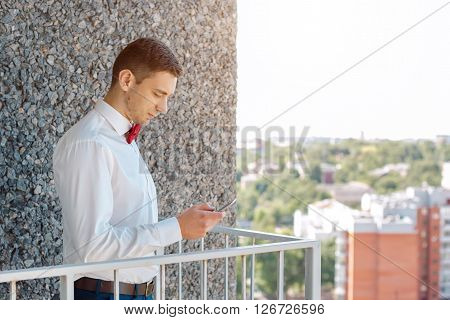 Portait of a young handsome man with smartphone texting sms. Gorgeous guy on gray background