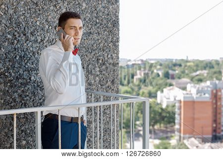 Portait of a young handsome man calling. Gorgeous guy on gray background