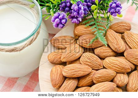 Almond milk with almond on a tablecloth.