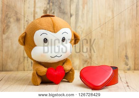 Happy Smiling Monkey Doll Hugging Red Heart With Gift Box Sitting On Wood, Gift Of Love Concept