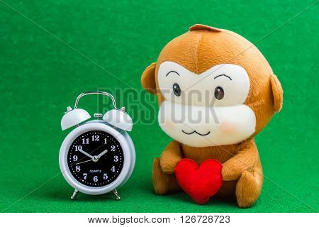 Happy Smiling Monkey Doll Hugging Red Heart, With Classic Alarm Clock Sitting On Green Background Gi
