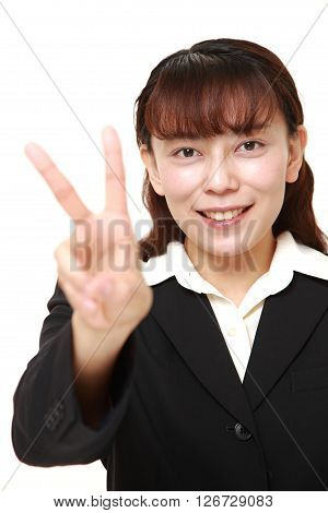 Asian Businesswoman showing a victory sign on white background