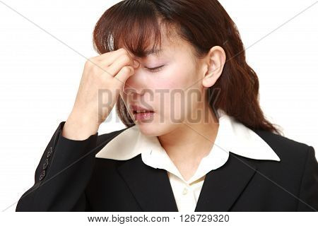 Asian businesswoman suffers from Asthenopia on white background