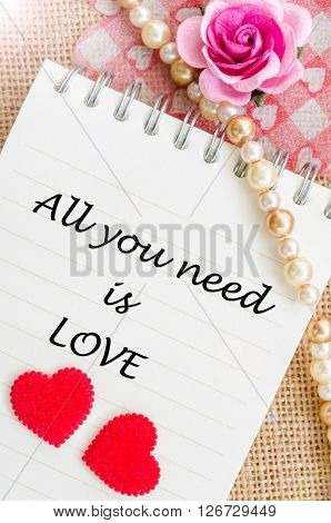 All you need is love on diary with red heart and rose on sack background.