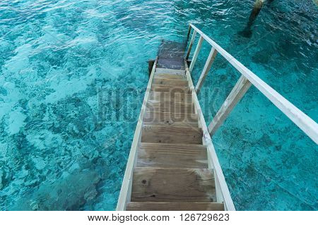 wood stair into the blue sea , Maldives
