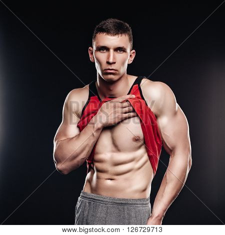 Sexy muscular fitness man showing sixpack muscles without fat over black background. Strong athletic man fitness model lifts up shirt and reveals a muscular body