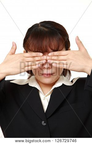 businesswoman covering her face with hands against white background