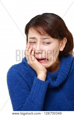 studio shot of Asian woman suffers from toothache on white background