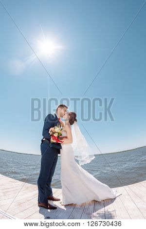 Bride and Groom, Kissing Against Sunshine on a Beautiful Pier, Romantic Married Couple