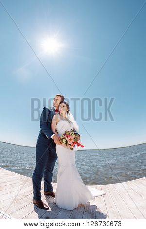 Bride and Groom, Posing Against Sunshine on a Beautiful Pier, Romantic Married Couple