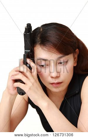 studio shot of woman with a handgun thinks on white background