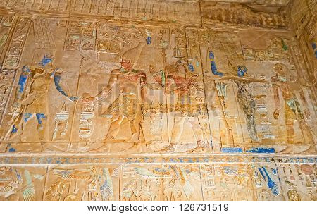 LUXOR EGYPT - OCTOBER 7 2014: The colorful reliefs with Gods and Pharaohs on the old walls of Karnak Temple complex on October 7 in Luxor.