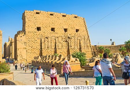 LUXOR EGYPT - OCTOBER 7 2014: The tourists next to the First Pylon of the Karnak Temple with the alley of Ram Headed Sphinxes on the background on October 7 in Luxor.