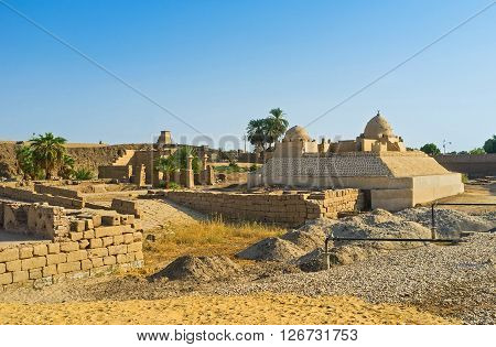 The old clay mosque among the ancient ruins located in front of the Karnak Temple Luxor Egypt.