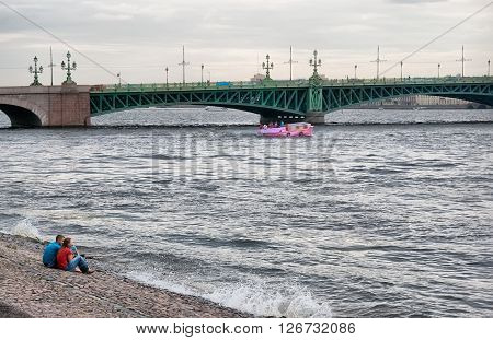 SAINT - PETERSBURG, RUSSIA - AUGUST 6, 2011: People sit on the bank of The Neva River near The Peter and Paul Fortress. On the background is a pink excursion boat in front of  The Troitskiy (Trinity) Bridge