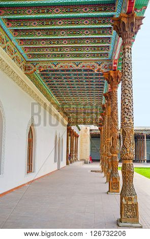 KOKAND UZBEKISTAN - MAY 6 2015: The scenic carved pillars and colorful canopy in the courtyard of the Jami Mosque covered with colorful floral patterns on May 6 in Kokand.