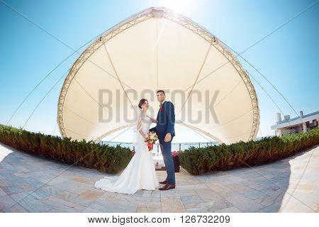 Young wedding couple enjoying romantic moments outside against modern buildings. Fisheye lens