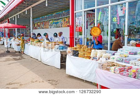 PUNGAN UZBEKISTAN - MAY 6 2015: The rustic food market with the wide range of lochira (traditional flat bread) sundried cheese balls (kurt) and sweets on May 6 in Pungan.