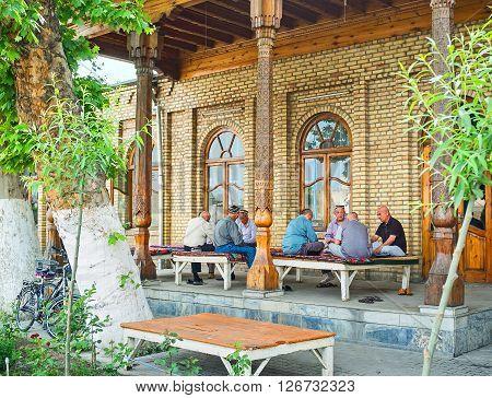 KOKAND UZBEKISTAN - MAY 6 2015: The locals enjoy the shady terrace of the teahouse on May 6 in Kokand.