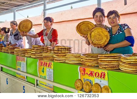 PUNGAN UZBEKISTAN - MAY 6 2015: The young merchants poses with the toasted lochira flat breads in rustic food market on May 6 in Pungan.