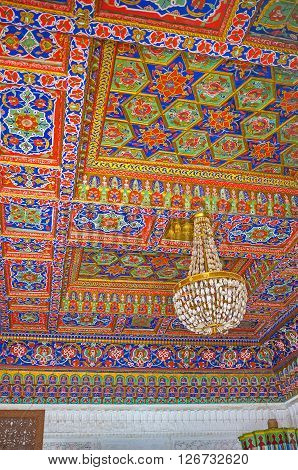 KOKAND UZBEKISTAN - MAY 6 2015: The ceiling in room of Khudayar Khan Palace with colorful floral and stellar patterns on the carved wood on May 6 in Kokand.