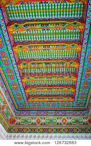 KOKAND UZBEKISTAN - MAY 6 2015: The ceiling in the Khudayar Khan Palace decorated with the wooden carvings and colorful arabesques on May 6 in Kokand.